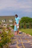 Flores molhando bonitos pequenas da menina e do pai com Imagem de Stock Royalty Free