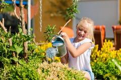 Flores molhando da criança feliz Imagens de Stock