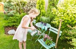 Flores molhando da menina da criança exteriores em um jardim do verão Fotografia de Stock Royalty Free