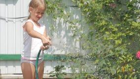 Flores molhando da menina em um jardim video estoque