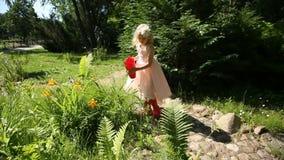 Flores molhando da menina em um jardim de uma lata molhando filme