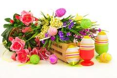 Flores na cesta de madeira com ovos da páscoa Imagens de Stock