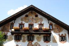 Flores nas janelas do balcão e fresco em Oberammergau em Alemanha Foto de Stock Royalty Free