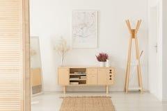 Flores no armário de madeira ao lado da cremalheira no salão de entrada branco interior com cartaz imagem de stock