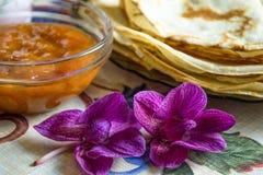Flores no primeiro plano e panquecas com doce Fotografia de Stock Royalty Free