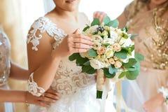 Flores, noiva e damas de honra do casamento guardando o ramalhete no dia do casamento Conceito feliz do casamento imagens de stock royalty free