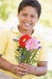 Flores novas da terra arrendada do menino Fotografia de Stock Royalty Free
