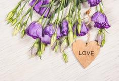 Flores púrpuras delicadas y un corazón de madera Concepto romántico Foto de archivo libre de regalías