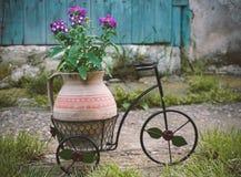 Flores p?rpuras en un pote de arcilla fijado en una bicicleta, decoraci?n para el jard?n fotos de archivo libres de regalías