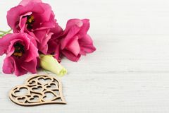 Flores púrpuras rosadas del eustoma y corazón de madera Fotos de archivo
