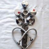 Flores para o dia de Valentim do St do encanador no coração do amor das mangueiras da água em uma trança do metal, uma chave ingl foto de stock royalty free