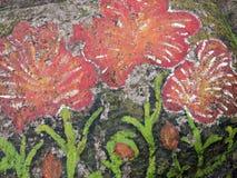 Flores pintadas na pedra velha fotografia de stock