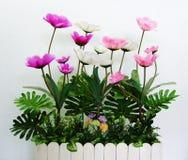 Flores plásticas em uma caixa de madeira do cerca-estilo Imagens de Stock Royalty Free