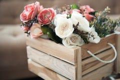 Flores plásticas en la caja de madera Foto de archivo libre de regalías
