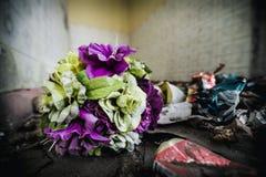 Flores plásticas viejas en un piso en un cuarto abandonado de la casa Fotos de archivo