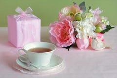 Flores preciosas con el regalo y la taza de té Foto de archivo
