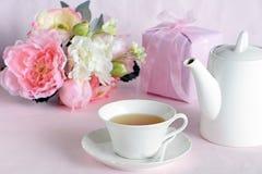Flores preciosas con el regalo y la taza de té Foto de archivo libre de regalías