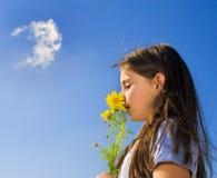 Flores que huelen de la chica joven Fotografía de archivo libre de regalías