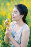 Flores que huelen de la mujer asiática Imágenes de archivo libres de regalías