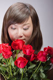 Flores que huelen de la mujer asiática hermosa Fotografía de archivo