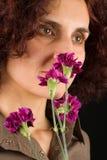 Flores que huelen de la mujer del Redhead Foto de archivo libre de regalías