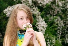 Flores que huelen del adolescente femenino joven en un jardín Imagenes de archivo