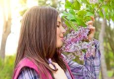 Flores que huelen del adolescente lindo en parque de la primavera Fotos de archivo libres de regalías