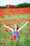Flores que lanzan de la muchacha en el aire Imágenes de archivo libres de regalías