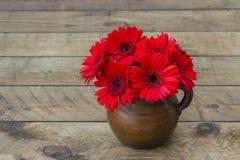Flores rojas del gerbera en un florero Imagen de archivo