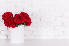 Flores rojas en florero sobre la pared de ladrillo blanca imágenes de archivo libres de regalías