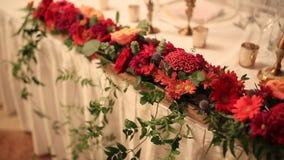 Flores rojas en la tabla de los recienes casados en el banquete de la boda almacen de metraje de vídeo