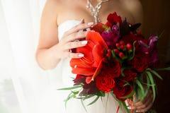 Flores rojas en las manos nupciales Imagen de archivo