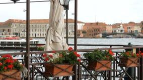 Flores rojas hermosas en potes en un terraplén de Grand Canal en Venecia en el fondo un barco que pasa a través con almacen de video