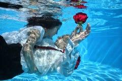 Flores rojas que se zambullen de la boda subacuática de novia que se besan y del novio Imágenes de archivo libres de regalías