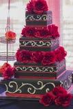 Flores rojas y pastel de bodas negro Fotos de archivo