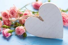 Flores rosadas blandas de las rosas y corazón blanco decorativo en textur Fotos de archivo libres de regalías