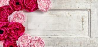 Flores rosadas de la vendimia en puerta envejecida Foto de archivo