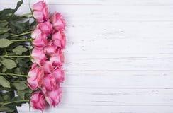 Flores rosadas de las rosas en el fondo de madera blanco Visión superior Fotos de archivo libres de regalías