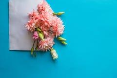 Flores rosadas del crisantemo y flores del ranúnculo, regalo o presente, sobre en fondo azul Día de madres, cumpleaños foto de archivo