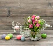 Flores rosadas del tulipán y huevos de Pascua coloreados Cuadro retro del estilo Fotos de archivo