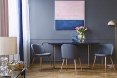 Flores rosadas en la tabla en interior del comedor con la pintura y Foto de archivo
