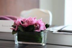 Flores rosadas en una tabla de la sala de reunión Imágenes de archivo libres de regalías
