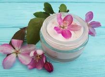 Flores rosadas hechas a mano de la loción de la crema hidratante de la protección de la magnolia de cristal cosmética poner crema Fotos de archivo libres de regalías