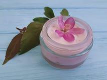 Flores rosadas hechas a mano de la loción de la protección de la magnolia de cristal cosmética poner crema de la esencia en de ma Foto de archivo libre de regalías