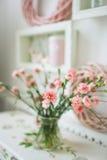 Flores rosadas hermosas en un florero en la tabla rústica blanca Imagenes de archivo