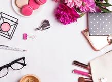 Flores rosadas, macarons, accesorios femeninos en el blanco Fotos de archivo libres de regalías