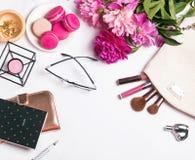Flores rosadas, macarons, accesorios femeninos en el blanco Fotografía de archivo