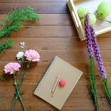 Flores rosadas y púrpuras dulces con el cuaderno y los lápices en el fondo de madera de la tabla Foto de archivo libre de regalías