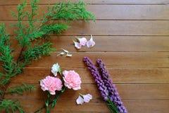 Flores rosadas y púrpuras dulces en el fondo de madera de la tabla Fotos de archivo