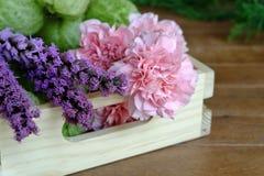 Flores rosadas y púrpuras dulces en la tabla de madera Foto de archivo